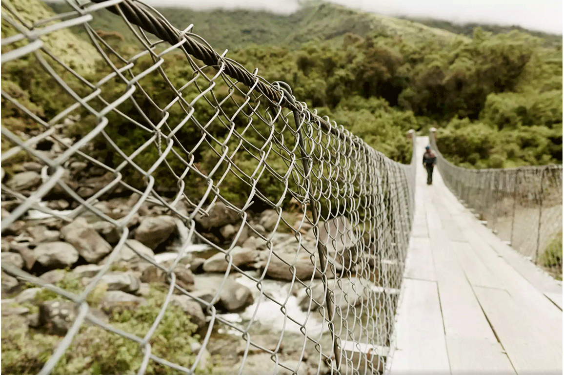 suspended bridge in bolivia with man walking on it