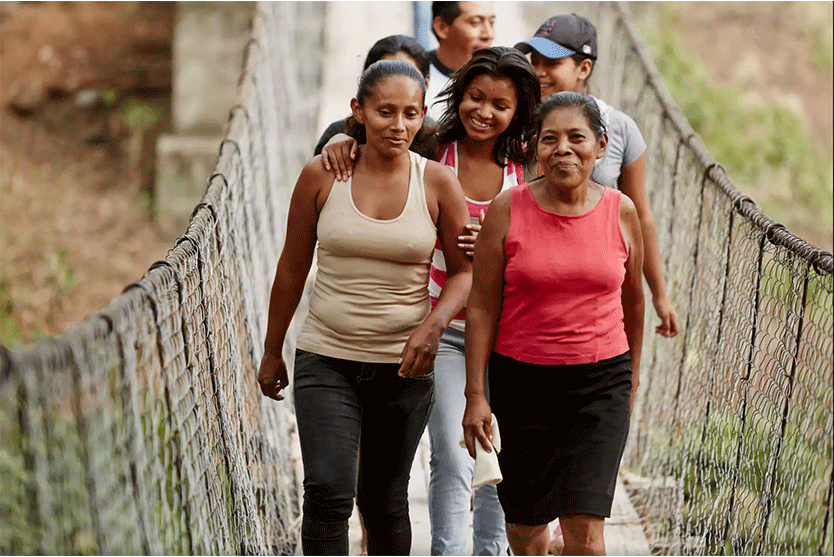 women walking on suspended bridge in tan and red tank tops