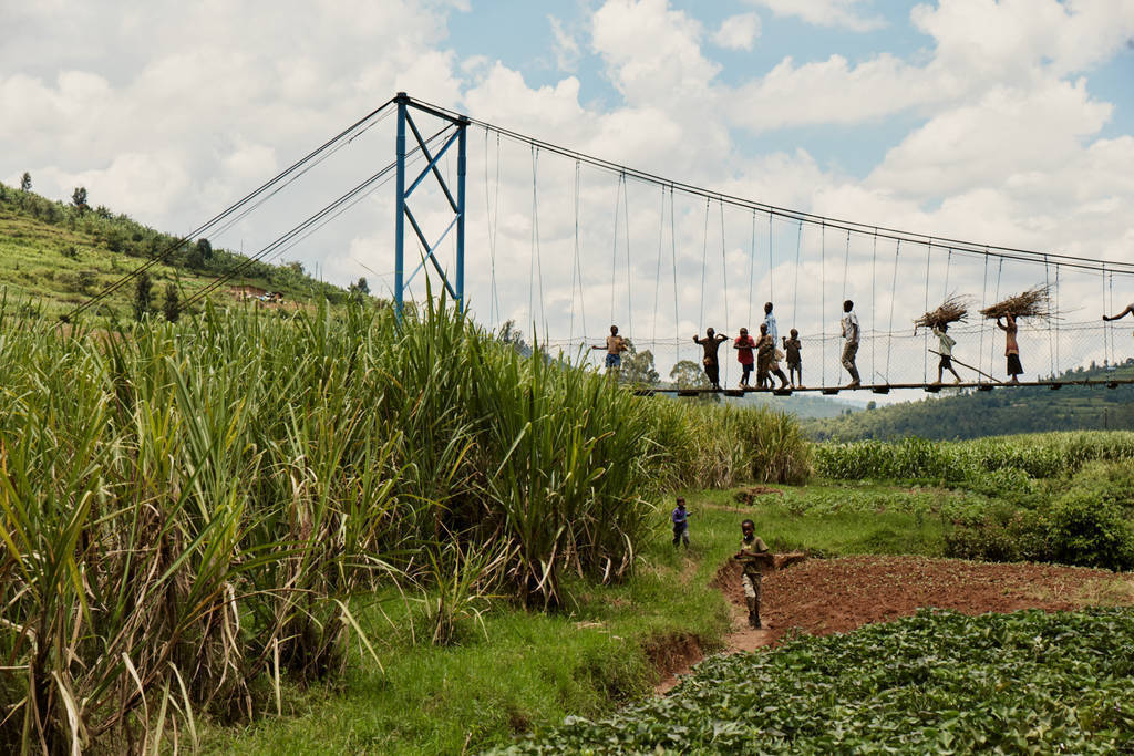 suspension footbridge over flood plain with lots of people crossing people in filed below crops all around blue sky white clouds